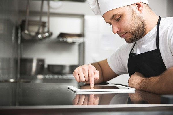 chef in kitchen with tablet